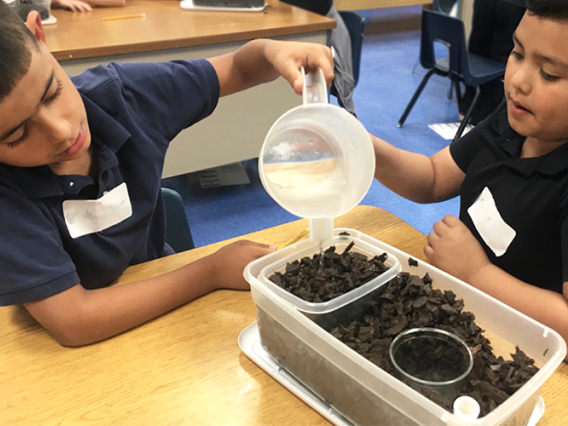 Students pouring water on 4th grade groundwater model